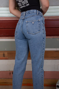 model is wearing mid wash blue denim jeans made by guess these jeans feature the iconic tringale logo on t he back and are slightly high waisted