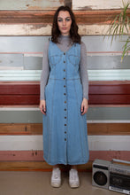 Load image into Gallery viewer, model is wearing a denim dress which features brass buttons going all the way down. The dress is a light to mid wash denim with two pockets on either side of the dress