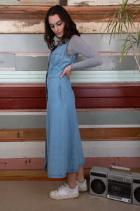 model is wearing a denim dress which features brass buttons going all the way down. The dress is a light to mid wash denim with two pockets on either side of the dress
