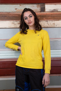 model is wearing a yellow long sleeve top made by ralph lauren. The top features a navy logo