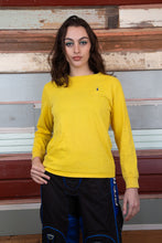 Load image into Gallery viewer, model is wearing a yellow long sleeve top made by ralph lauren. The top features a navy logo