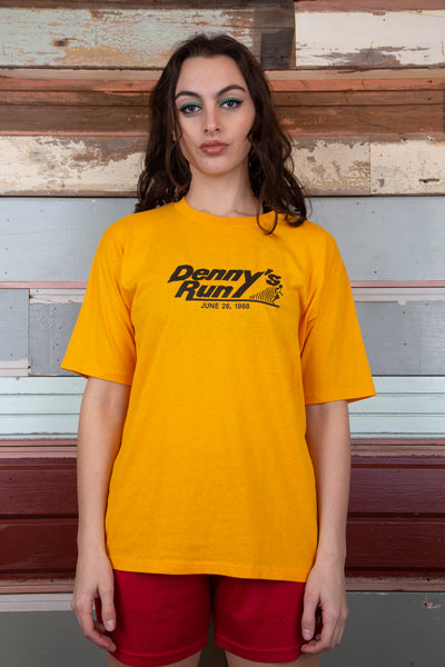 model is wearing a yellow shirt from 1988, the shirt says Denny's run and on the back advertises PEPE