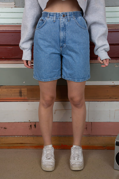 model is wearing some Lee denim shorts that feature an elastic waistband and no pockets on the back, the wash of the denim is light to mid wash