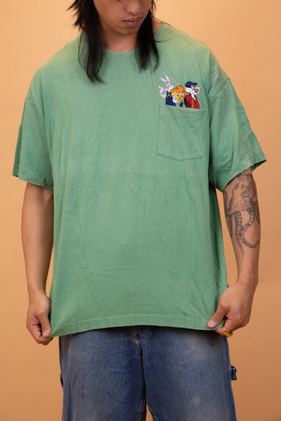 The model is wearing a green top that features an embroidered with the friendly Loony Tunes in the pocket