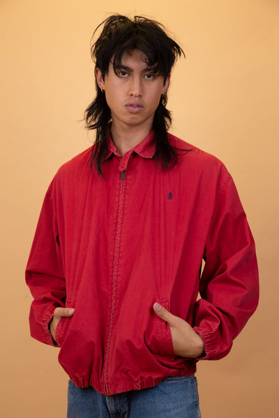 Red Ralph Lauren Coach Jacket with a zip closure, pockets, folded collar and navy blue Ralph Lauren branding on the left chest.