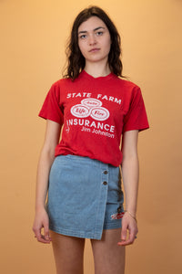 "red tee with ""state farm insurance"" graphic on the front in white."