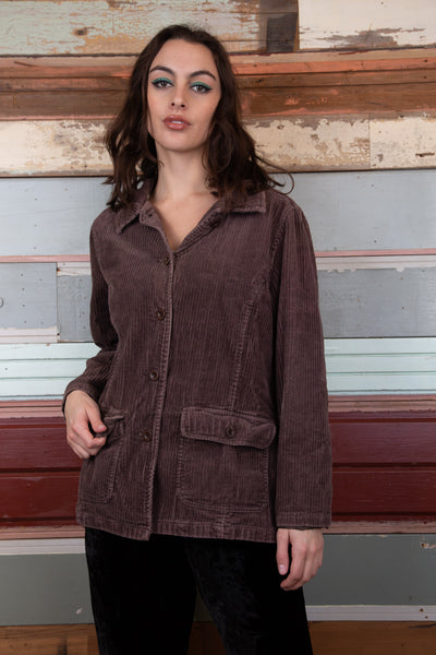model is wearing a brown corduroy blazer that features two big pockets either side of the buttons.