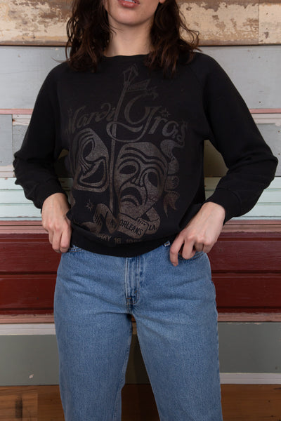 model is wearing a black sweater that features a black print showing the 1988 Mardi Gras