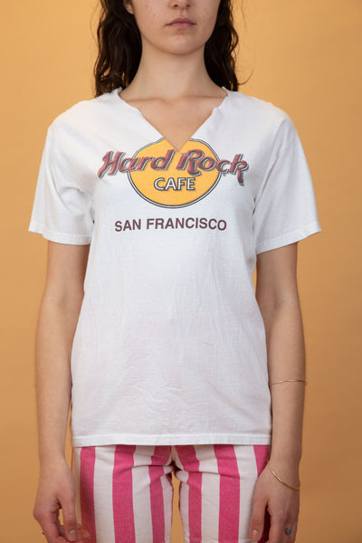 "white tee with ""hard rock cafe san francisco"" on the front. Neckline has been cut into a v-neck"