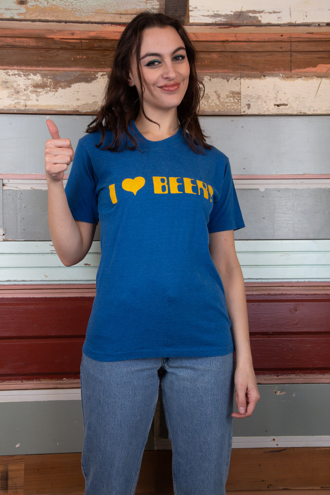 model is wearing a blue tee that features a printed logo on the front saying