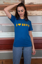 "Load image into Gallery viewer, model is wearing a blue tee that features a printed logo on the front saying ""I HEART BEER"""