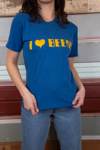 "model is wearing a blue tee that features a printed logo on the front saying ""I HEART BEER"""