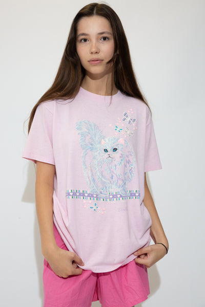 Pink single-stitch tee with a large, textured cat print on the front with diamanté pupils and butterflies surrounding it. Dated 1988 at the bottom while repping Dallas.