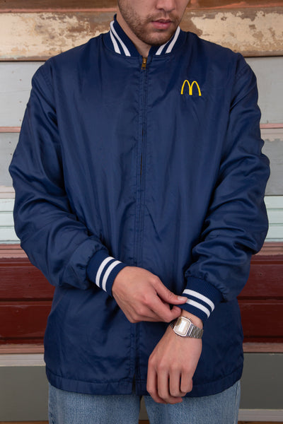 navy jacket with white striped detailing on neck and cuffs, along with embroidered M mcdonalds logo on left chest