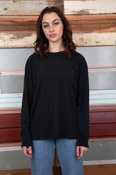 model is wearing a black long sleeve top, the top features a small pocket on the top left by the chest that has a small red ralph lauren logo