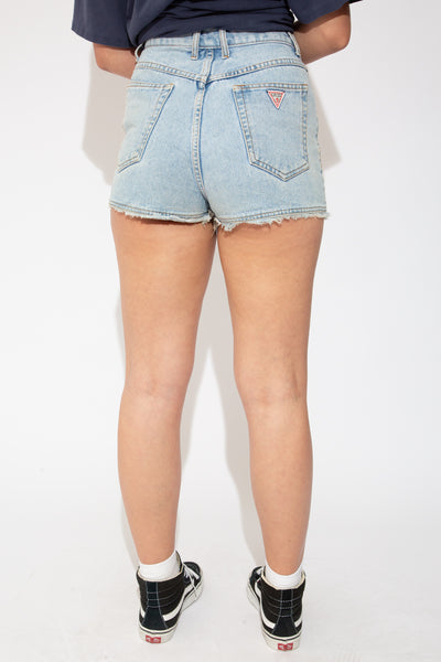 Light-wash blue shorts with light brown stitching, frayed hems and branding on the button and back pocket. 80's Guess jeans label on inner waistline and back pocket.