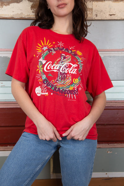 red tee with fun coca cola graphic on front and sponsored logos on back