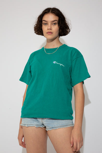 Green tee with an oversized fit, single-stitching and Champion branding on the left chest and left sleeve.