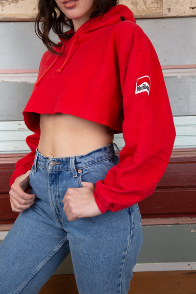 the model is wearing a red cropped sweater that features a small logo on the left sleeve