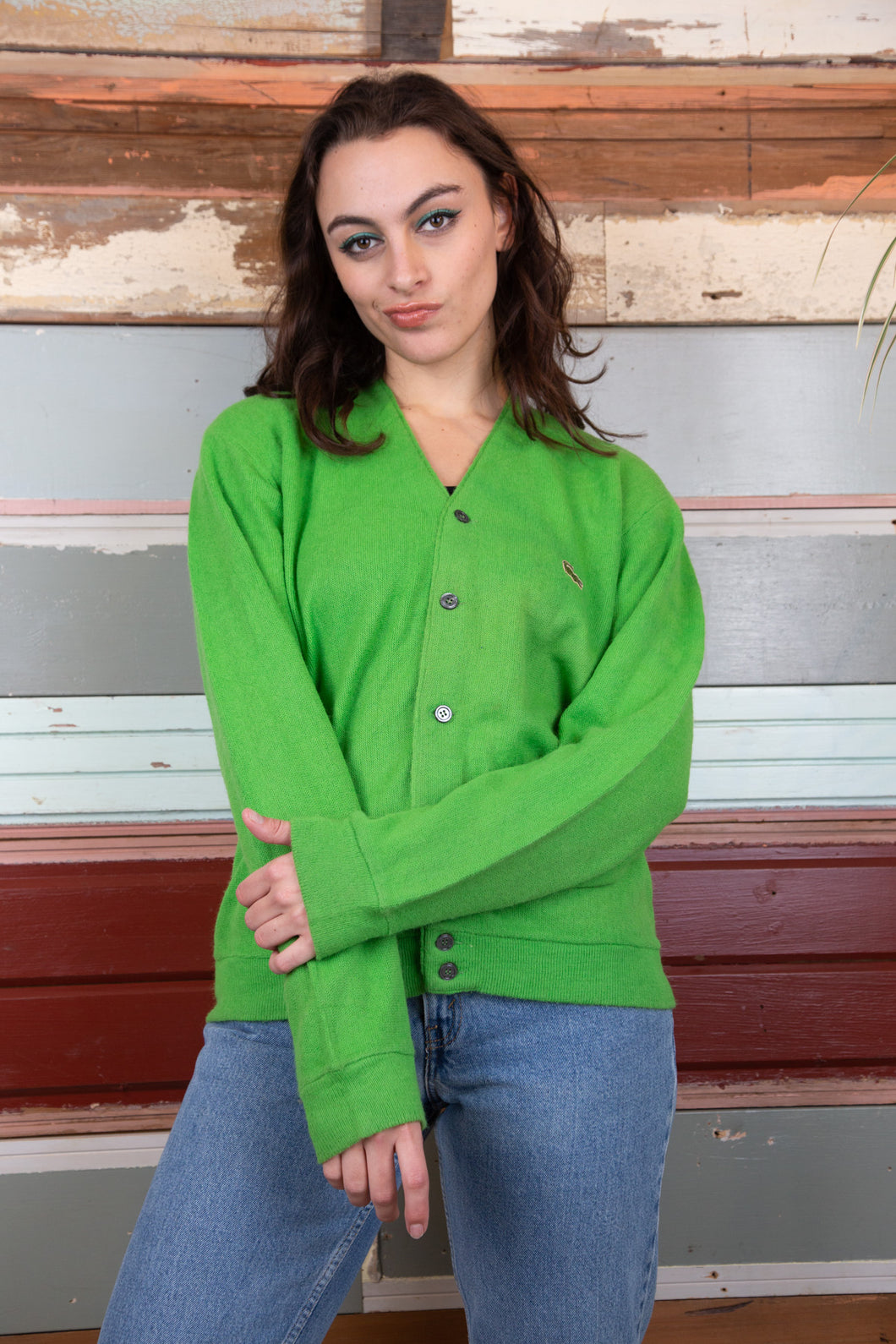 the model is wearing a green knitted sweater made from lacoste, this sweater fits oversized.