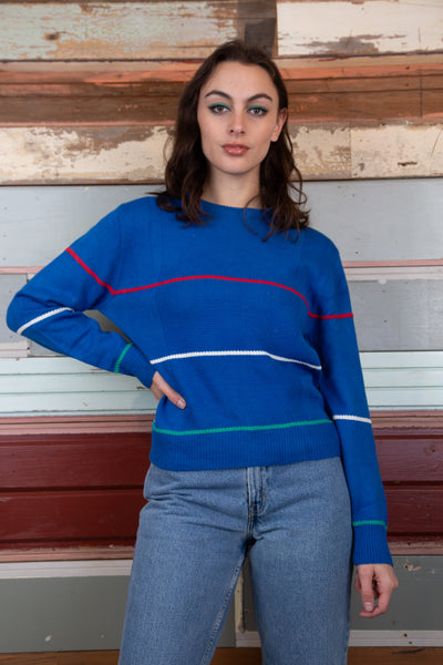the model is wearing a blue Lacoste knitted sweater that features three stripes of the colours red, white and green.