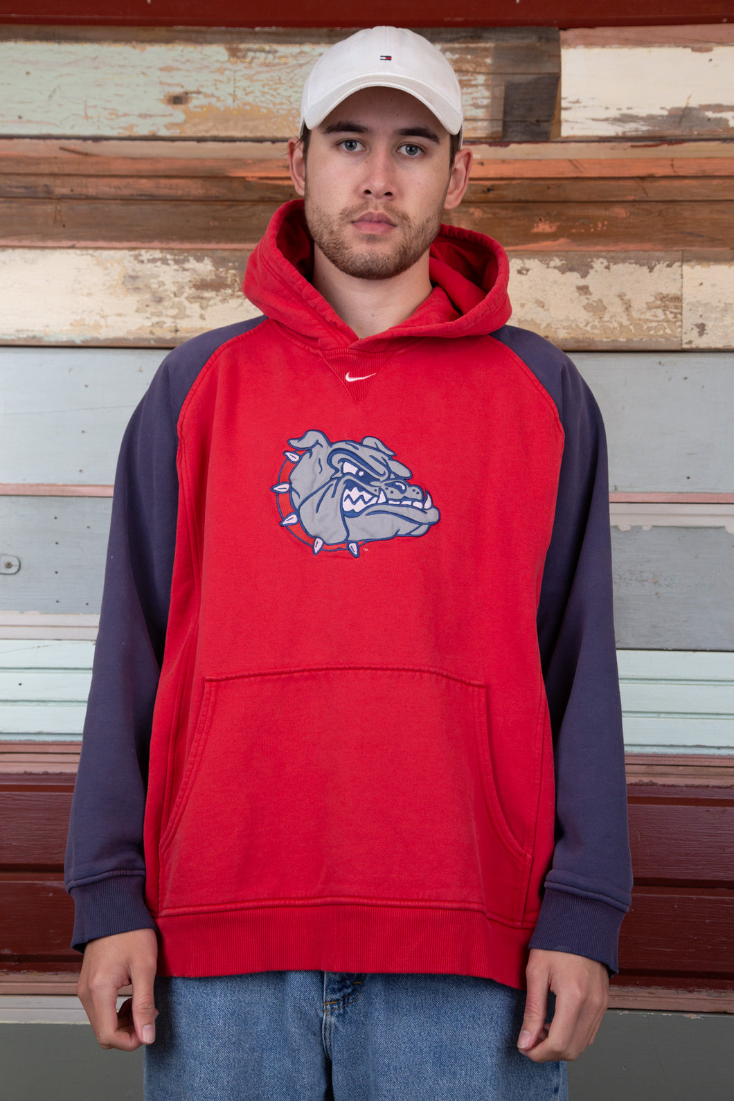 red hoodie with contrasting navy/indigo sleeves and large bulldog applique graphic on chest and small embroidered nike tick above