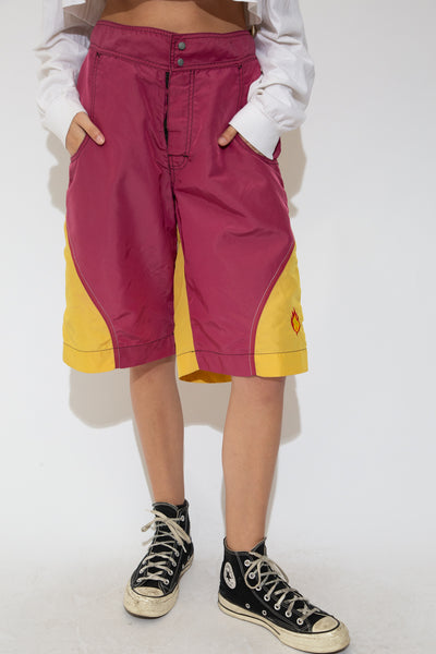 With maroon and yellow colours and large front and back pockets in a midi-length fit, these shorts are the ultimate 2000s throwback. Finished off with velcro and dome closures and black stitching.