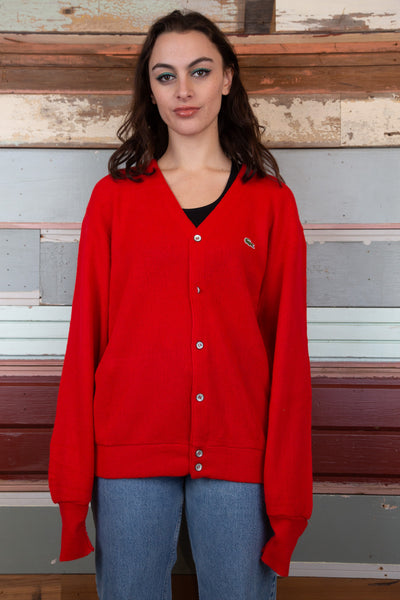 model is wearing a red Lacoste cardigan that fits slightly oversized.