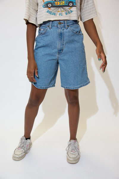 The model is wearing a pair of ligthwash vintage denim shorts