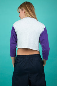 This Champion crop is grey with purple contrast sleeves, a purple candy striped pattern along the neckline and a purple 'Champion' on the right chest. The neckline is loose-fitting and the arms are mid-length.