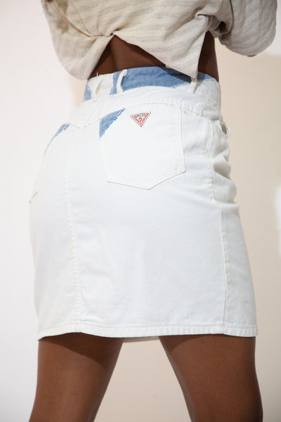 The model is wearing a white skirt that features the guess triangle logo on the back right pocket.