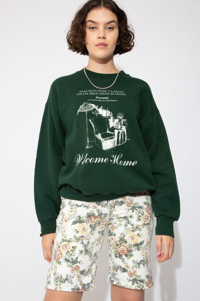 Dark green sweater with white print of a home scene and 'welcome home' printed below. Machon Bais Yaakov Hilda Birn High School printed above.
