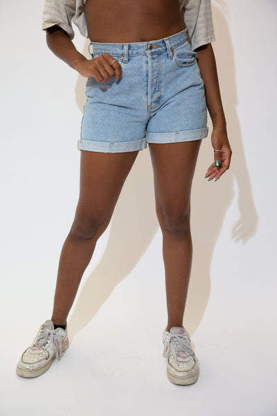 The model is wearing light wash denim shorts with a cuff at the bottom. These light wash blue denim shorts are made by GAP