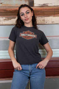 the model is wearing a black Harley Davidson tee with the iconic Harley logo with a simple white back print.