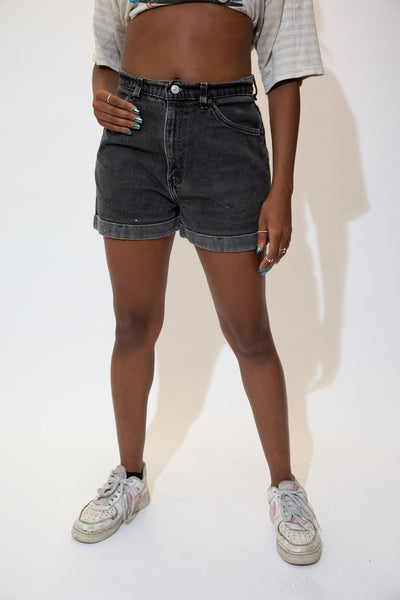 The model is wearing a pair of black denim vintage shorts made by Levis.