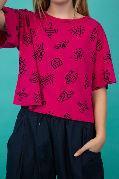 This bright fuchsia pink top is cropped mid-length and decorated with a cool abstract print.