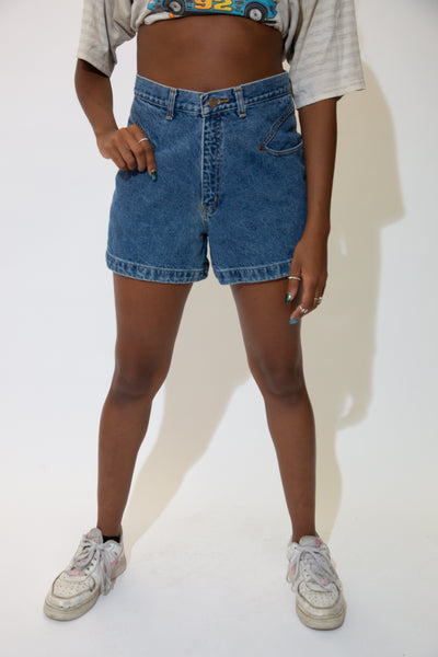 The model is wearing a pair of dark wash denim shorts that feature slanted pockets on the front.