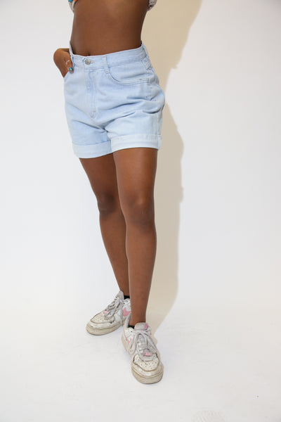 The model is wearing Riders light blue denim shorts that have a stitched fold