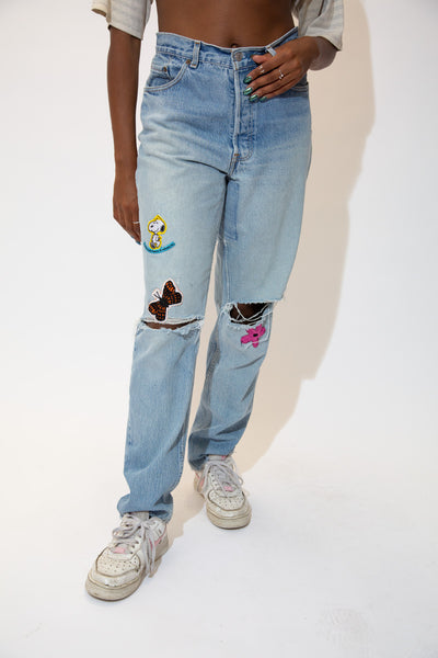 The model is wearing a pair of lightwashjeans with a snoopy patch