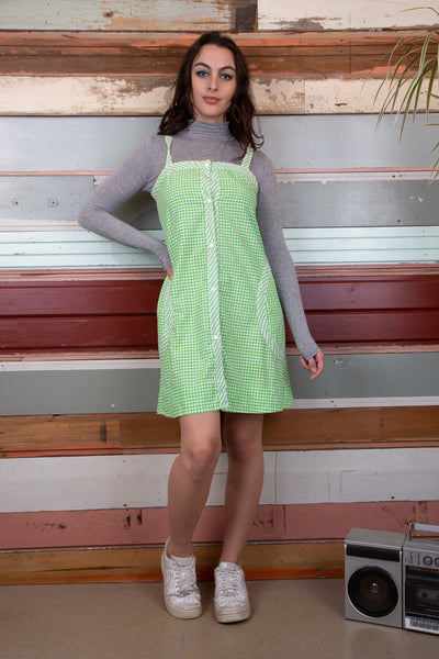 model is wearing a green and white checked dress with wide straps details on the dress include buttons going all the way down
