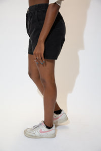 The model is wearing a pair of black OP shorts that feature a elastic waist  band