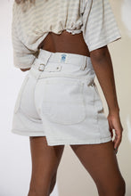 Load image into Gallery viewer, The model is wearing a cream pair of vintage Riders denim shorts, the shorts feature a back strap