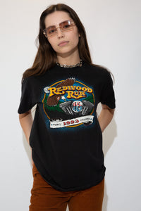 Black in colour with a  print of an eagle, motorcycle engine and a green landscape on the front. With a yellow spellout of Redwood Run and Dated 1993 California below. Orange print of biker gang names on back. \
