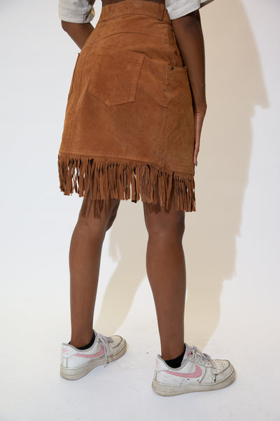 The model is wearing a brown leather skirt that features tassels on the lower bit of the skirt