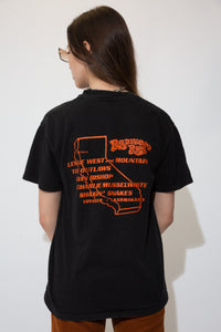 Black in colour with a  print of an eagle, motorcycle engine and a green landscape on the front. With a yellow spellout of Redwood Run and Dated 1993 California below. Orange print of biker gang names on back.