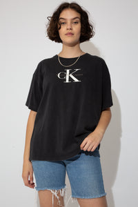 This black Calvin Klein Jeans tee has a classic design, single-stitching and CK branding in white and grey on the front. Stretched out neckline adds to baggy fit.