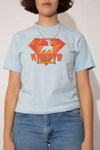 Light blue, short-sleeved tee with a print of Krypto the Superdog and the Superman 'S' logo behind him. Spellout below.