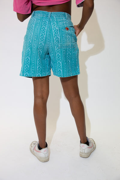 The model is wearing a pair of teal cord vintage shorts made by gotcha!