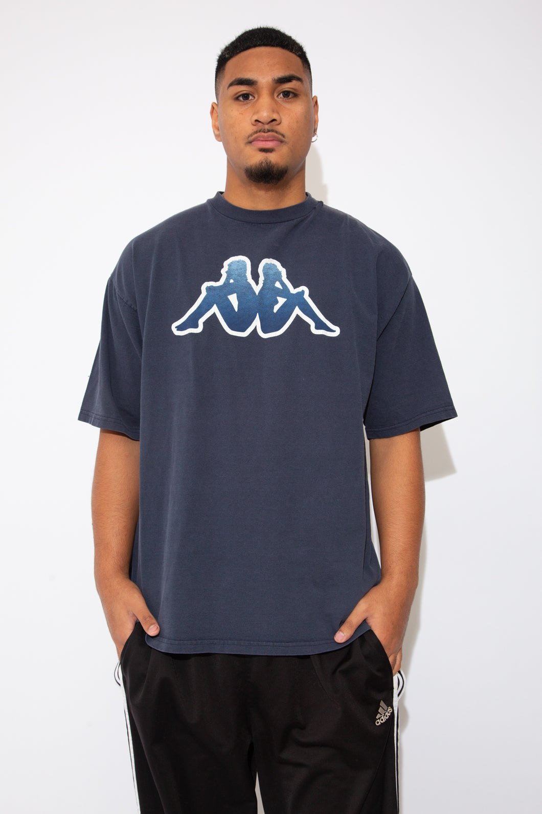 model is wearing a navy blue top that fits slightly oversized on the model, the tee features the Kappa logo on the center which has slightly cracked.