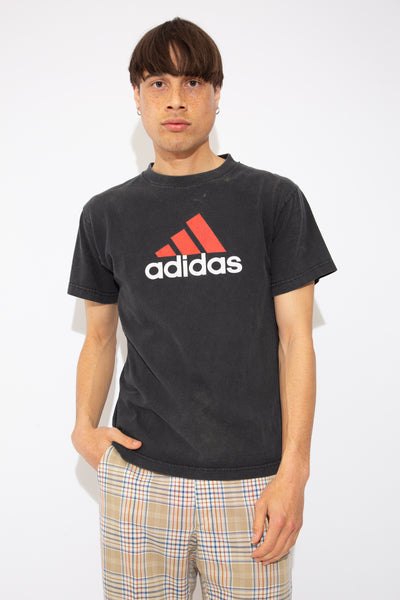model is wearing a black tee featuring the Adidas logo on the front in red, the tee has small bleach marks on the top left side near the collar.
